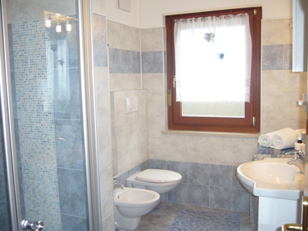 bagno con doccia, water, bidet, lavandino con specchio e lavatrice.